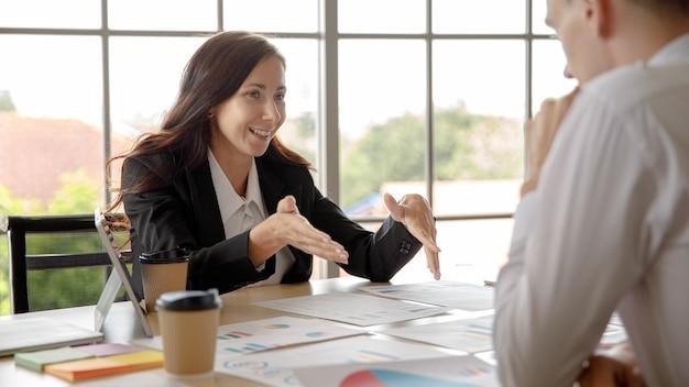 Responsabile caucasico della donna di affari che si siede sorridente preparando spiegare presentando l'analisi statistica dati finanziari informazioni rapporto documenti scartoffie sul desktop al collega dell'uomo d'affari in ufficio.