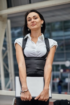 Una donna d'affari caucasica con laptop all'aria aperta