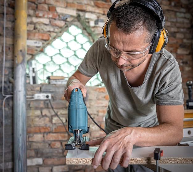Un falegname caucasico si sta concentrando sul taglio del legno con un seghetto alternativo nel suo laboratorio.