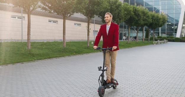 Giovane alla moda felice allegro caucasico in giacca rossa in sella a scooter elettrico e in piedi ancora sulla strada in città. cavaliere maschio sorridente gioioso di bell'aspetto che va da qualche parte gita estiva in città
