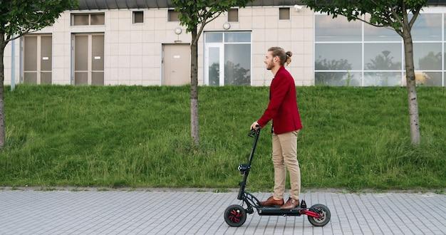 Giovane alla moda allegro caucasico in giacca rossa in sella a uno scooter elettrico e in piedi ancora sulla strada in città. cavaliere maschio di bell'aspetto che sorride e si diverte mentre va da qualche parte. gita in città.