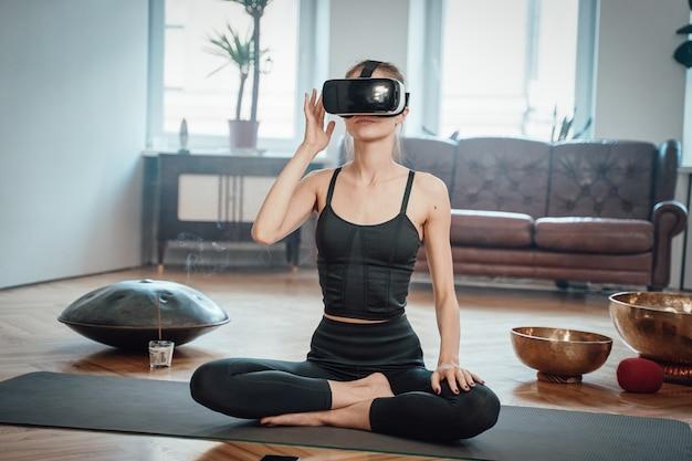 La donna allegra caucasica indossata con le cuffie da realtà virtuale medita facendo yoga nella posizione del loto seduto sul tappeto nel soggiorno durante il giorno.