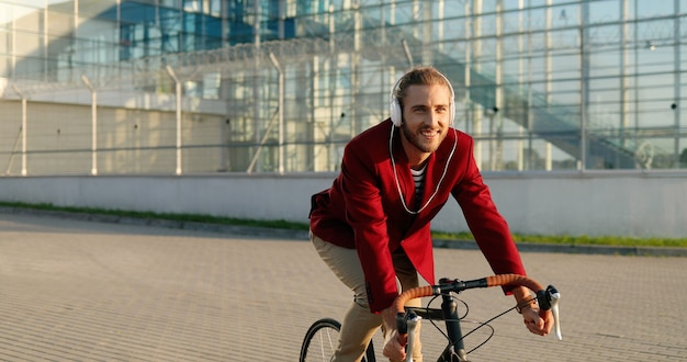 Ciclista maschio alla moda giovane allegro caucasico in giacca casual rossa e cuffie in sella a una bicicletta in strada. uomo sorridente gioioso felice bello avendo giro in bicicletta e ascoltare musica. panorama della città