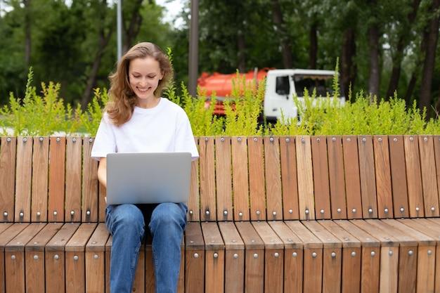 Caucasica giovane donna allegra che riposa nel parco su una panca di legno e chiacchiera nei social network, libero professionista esperto che si gode il lavoro a distanza digitando la pubblicazione per il blog web sul laptop