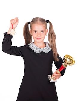 La ragazza caucasica del bambino tiene la tazza e la medaglia isolate su fondo bianco.