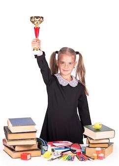 La bambina caucasica tiene la coppa e la medaglia isolate su una superficie bianca