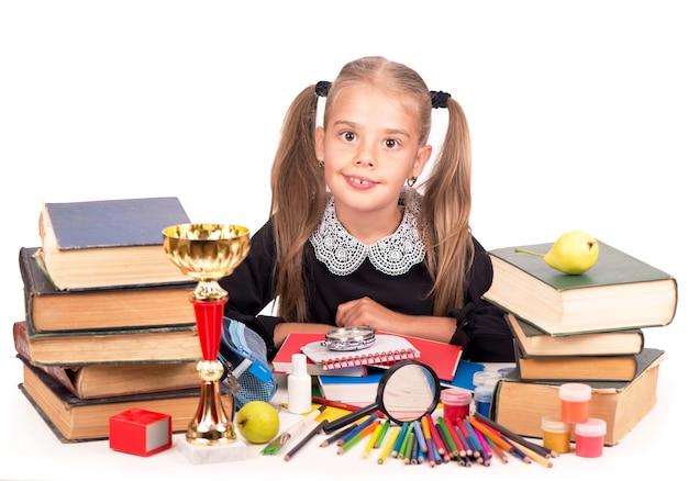 Ragazza caucasica del bambino con materiale scolastico stazionario isolato sulla superficie bianca