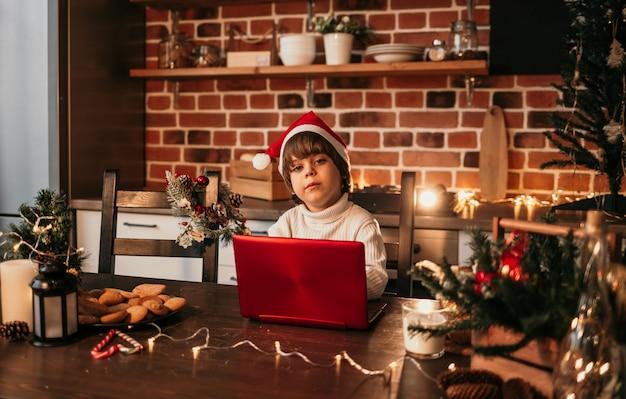Un bambino caucasico con un maglione bianco e un cappello di capodanno è seduto al tavolo della cucina e sta scrivendo un saluto di capodanno su un laptop