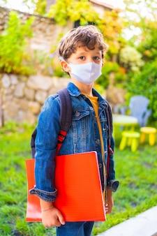 Bambino caucasico con maschera facciale pronta per tornare a scuola. nuova normalità, distanza sociale, pandemia di coronavirus, covid-19. giacca, zaino e un blocco rosso per le note in mano