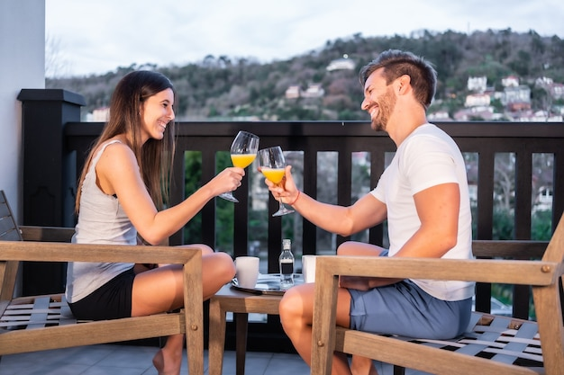 Una coppia caucasica facendo colazione sulla terrazza dell'hotel in pigiama. brindare con succo d'arancia al mattino, stile di vita di una coppia innamorata