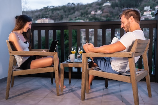 Una coppia caucasica che fa colazione sulla terrazza dell'hotel in pigiama guardando il telegiornale sul cellulare. fare colazione con un succo d'arancia al mattino, stile di vita di una coppia innamorata