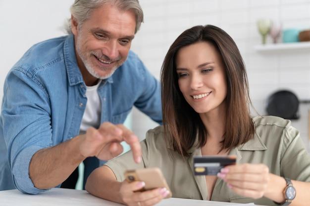 Coppia caucasica coinvolta nello shopping online, inserendo le informazioni di pagamento dalla carta di credito nell'applicazione mobile