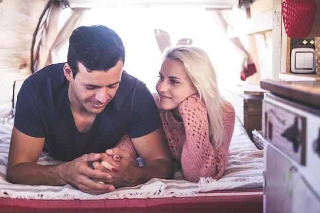 Coppia caucasica innamorata e scena romantica all'interno di un vecchio camper vintage pronto a viaggiare e fare una vacanza insieme alla felicità e alla gioia. bella modella bionda sdraiata e resta carina