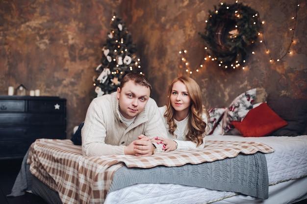 Coppia caucasica sdraiata sul letto con calde coperte sulla parete decorata con ghirlanda e corona.