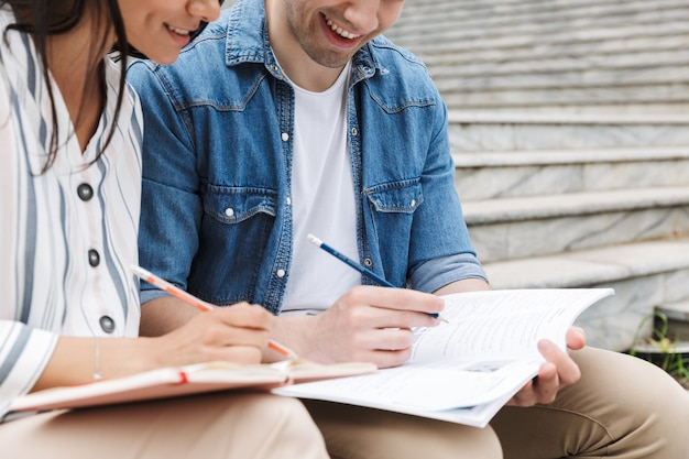 Coppia caucasica uomo e donna in abiti casual che parlano e studiano seduti su una panchina vicino alle scale all'aperto