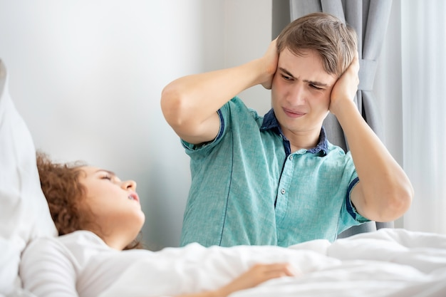 Coppie caucasiche in pigiama russare e dormire male sulla camera da letto. le sue orecchie di blocco con le mani.