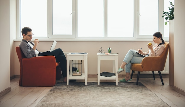 Coppia indoeuropea con abitudini sane, lavorando al computer portatile mentre si mangia una mela e la scrittura nel libro