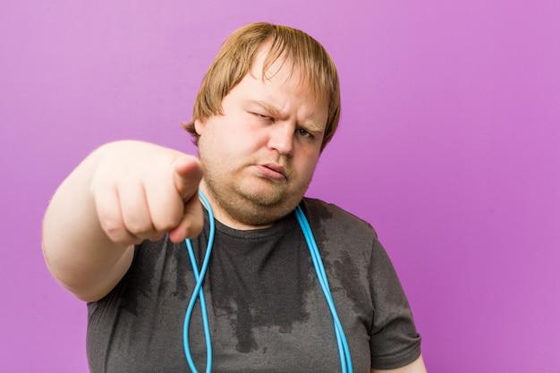 Uomo grasso biondo pazzo caucasico che suda con una corda per saltare
