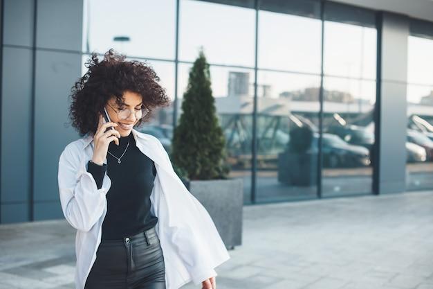 Donna di affari caucasica dai capelli riccia caucasica che parla sul telefono con un imprenditore fuori in una camicia bianca