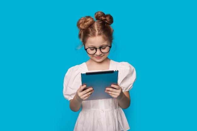 La ragazza carina caucasica sta leggendo da una tavoletta sorridente su una parete blu dello studio attraverso gli occhiali in un vestito bianco