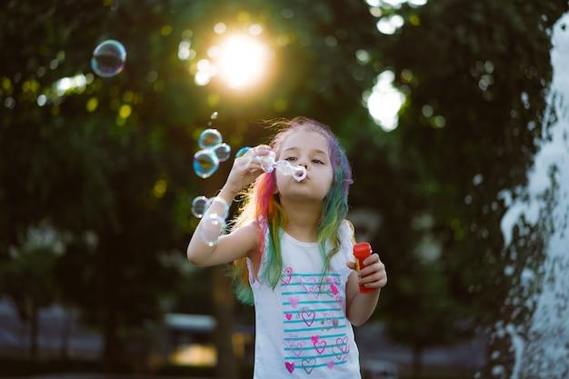 La bambina carina caucasica sta soffiando bolle di sapone nel parco