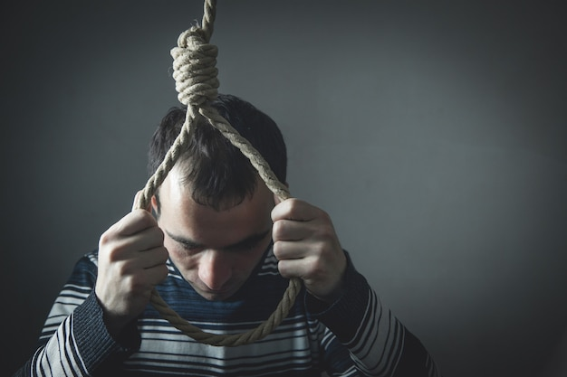 Uomo depresso caucasico con un cappio intorno al collo