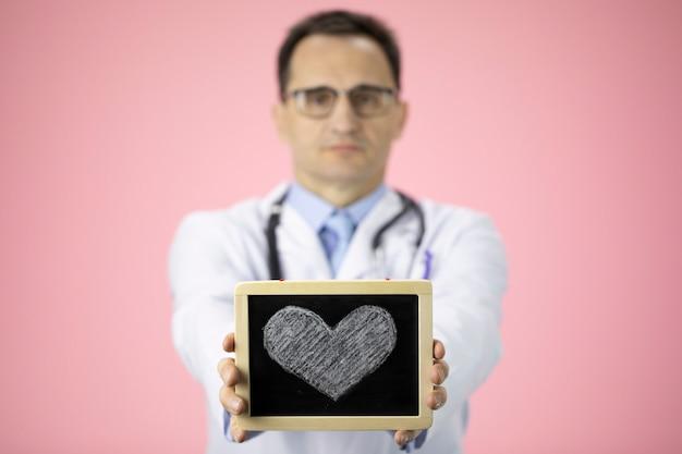 Il medico caucasico sul rosa tiene il cuore che attinge le mani tese