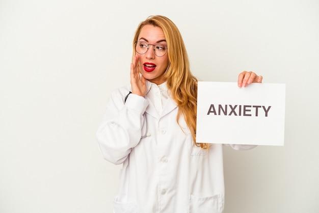 La donna caucasica del medico che tiene un cartello di ansia isolato su sfondo bianco sta dicendo una notizia segreta di frenata calda e sta guardando da parte