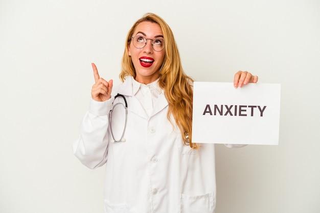 Donna caucasica del medico che tiene un cartello di ansia isolato su fondo bianco che indica al rialzo con la bocca aperta.