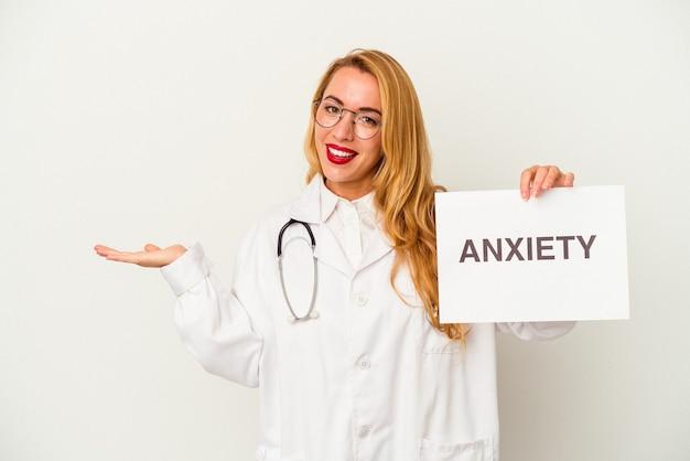 Donna caucasica del medico che tiene un cartello di ansia isolato su fondo bianco che mostra uno spazio della copia su una palma e che tiene un'altra mano sulla vita.