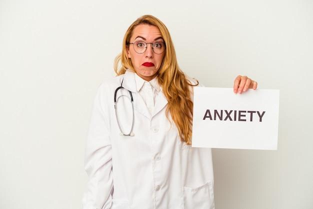 La donna caucasica del medico che tiene un cartello di ansia isolato su fondo bianco alza le spalle e apre gli occhi confusi.