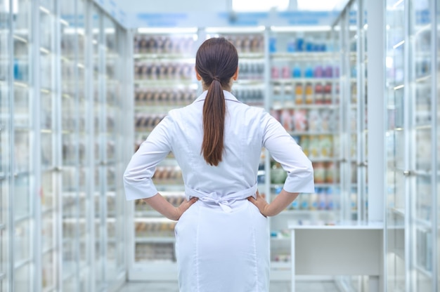 Farmacista caucasico guardando gli scaffali con integratori alimentari