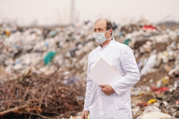 Ecologo caucasico in uniforme bianca che tiene appunti sotto l'ascella, camminando sulla discarica e stimando l'inquinamento.