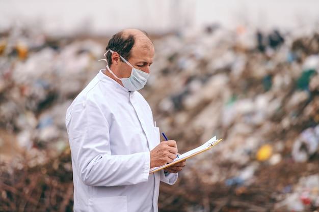 Ecologo caucasico in uniforme bianca in piedi scrivendo nei risultati degli appunti e stimando l'inquinamento in discarica.