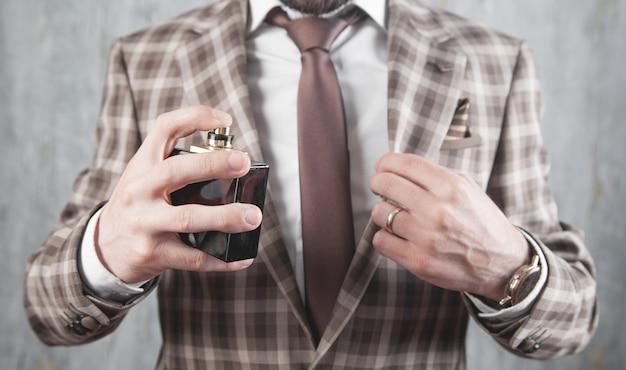 Uomo elegante caucasico che spruzza profumo.