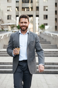 Imprenditore caucasico o uomo direttore in abito grigio, scendendo le scale del moderno centro business con caffè da asporto in mano