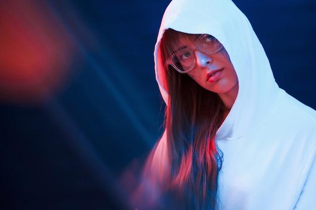 Etnia caucasica. studio girato in studio scuro con luce al neon. ritratto di giovane ragazza