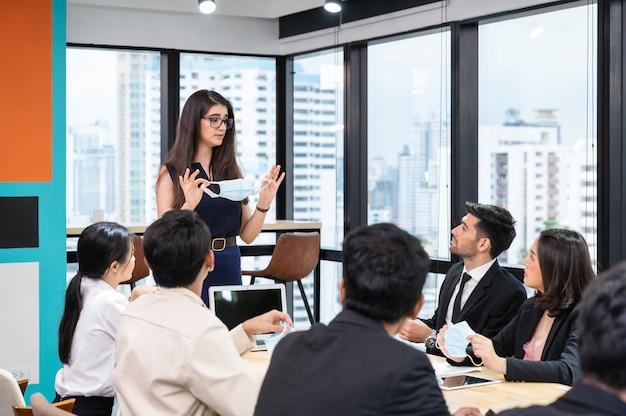 Il dirigente caucasico propone la politica aziendale sull'indossare la maschera facciale in azienda durante la riunione