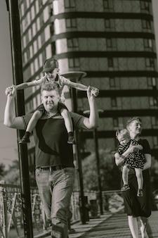 Le coppie caucasiche della famiglia che camminano con il padre dei bambini portano il figlio sulle spalle in bianco e nero