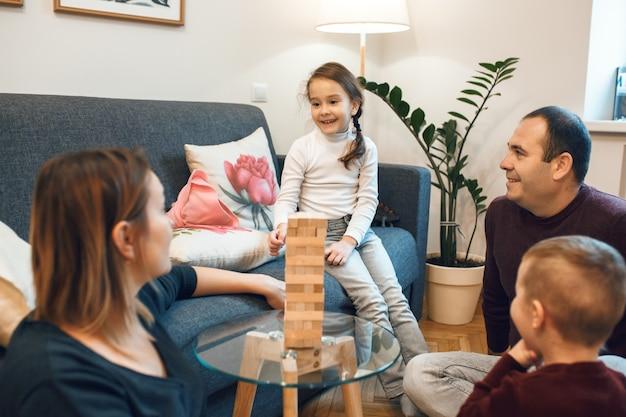 Famiglia caucasica che discute di qualcosa prima di iniziare a giocare al prossimo round di jenga