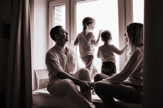 Famiglia caucasica che guarda fuori dalla finestra resta a casa durante la pandemia in bianco e nero