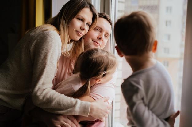 Famiglia caucasica che guarda fuori dalla finestra resta a casa durante la pandemia