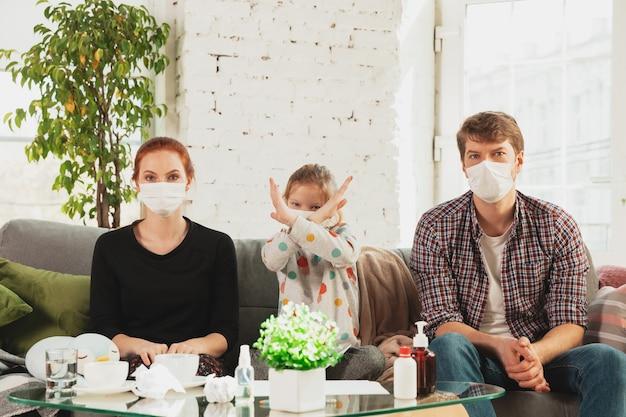 Famiglia caucasica in maschere protettive e guanti isolati a casa