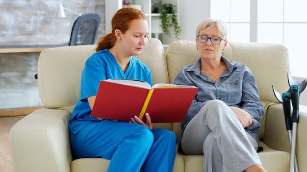 Assistente femminile caucasica nella casa di cura che legge un libro a un'anziana donna in pensione che si siede sul divano
