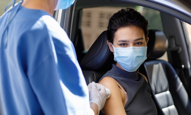 La dottoressa caucasica della sanità pubblica in uniforme ospedaliera blu e supporto per maschera facciale tiene l'iniezione dell'ago della siringa del vaccino sulla spalla del paziente della donna in viaggio attraverso la coda di vaccinazione dell'auto.