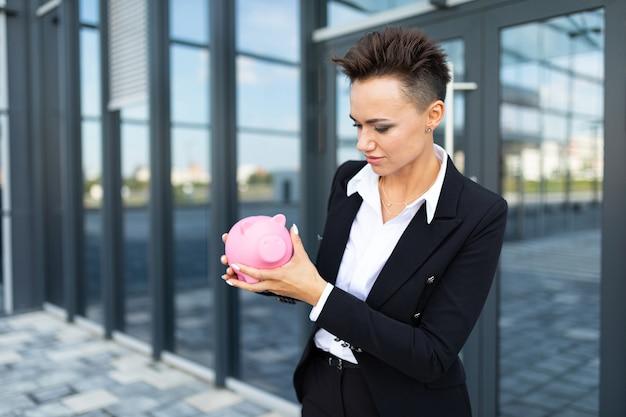 La femmina caucasica in vestiti in bianco e nero dell'ufficio tiene un salvadanaio rosa del maiale e aspetta un collega vicino all'edificio per uffici