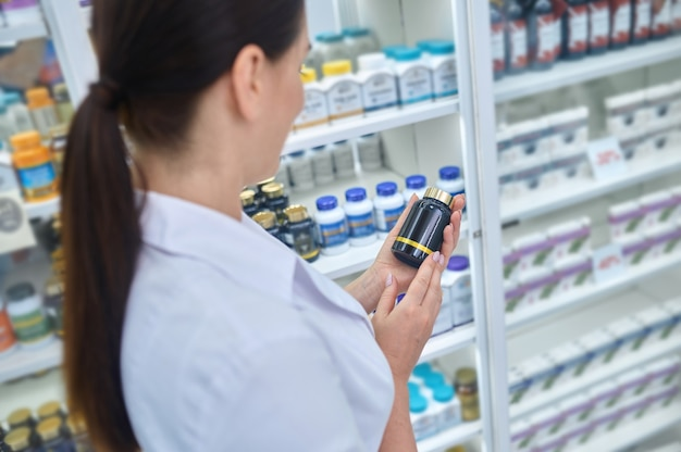 Farmacista femminile caucasica che esamina un integratore alimentare