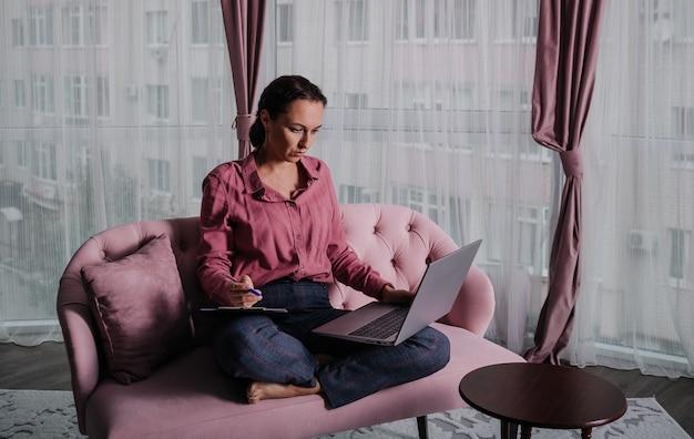 Una psicologa caucasica con una maglietta rosa è seduta sul divano e lavora su un laptop