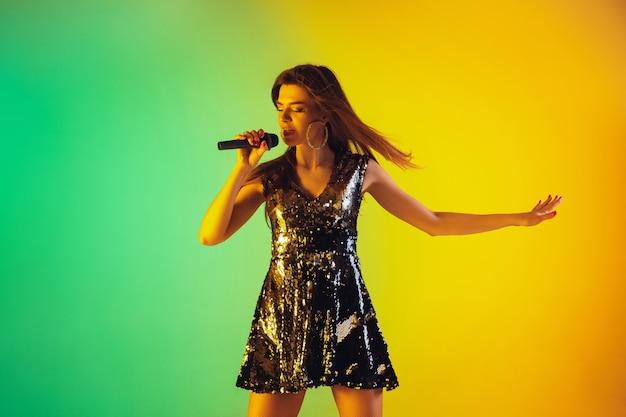 Ritratto di cantante femminile caucasico isolato su sfondo sfumato per studio in luce al neon