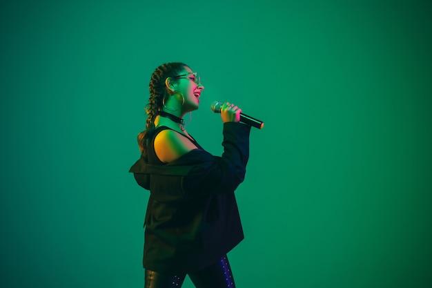 Ritratto femminile caucasico della cantante isolato sulla parete verde alla luce al neon. bellissimo modello femminile in abbigliamento nero con microfono.